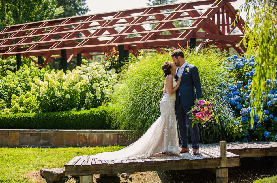 bride and groom kissing on Froggsong Garden Bridge with groom holding gorgeous bouquet from Herban Floral and Decor
