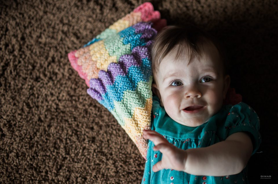Sweet baby girl of two mamas holding a crocheted rainbow blanket being photographed on the carpeted floor. photo by diwas photography